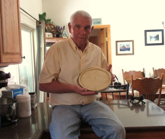 A man sits on the edge of a kitchen counter top, wearing jeans and a button-down collar shirt. He is holding up a homemade pie that is ready to go into the oven for baking.
