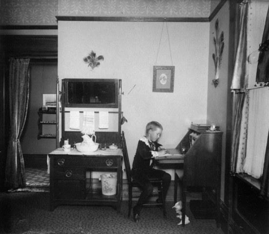 Child writing at desk, 1890-1900