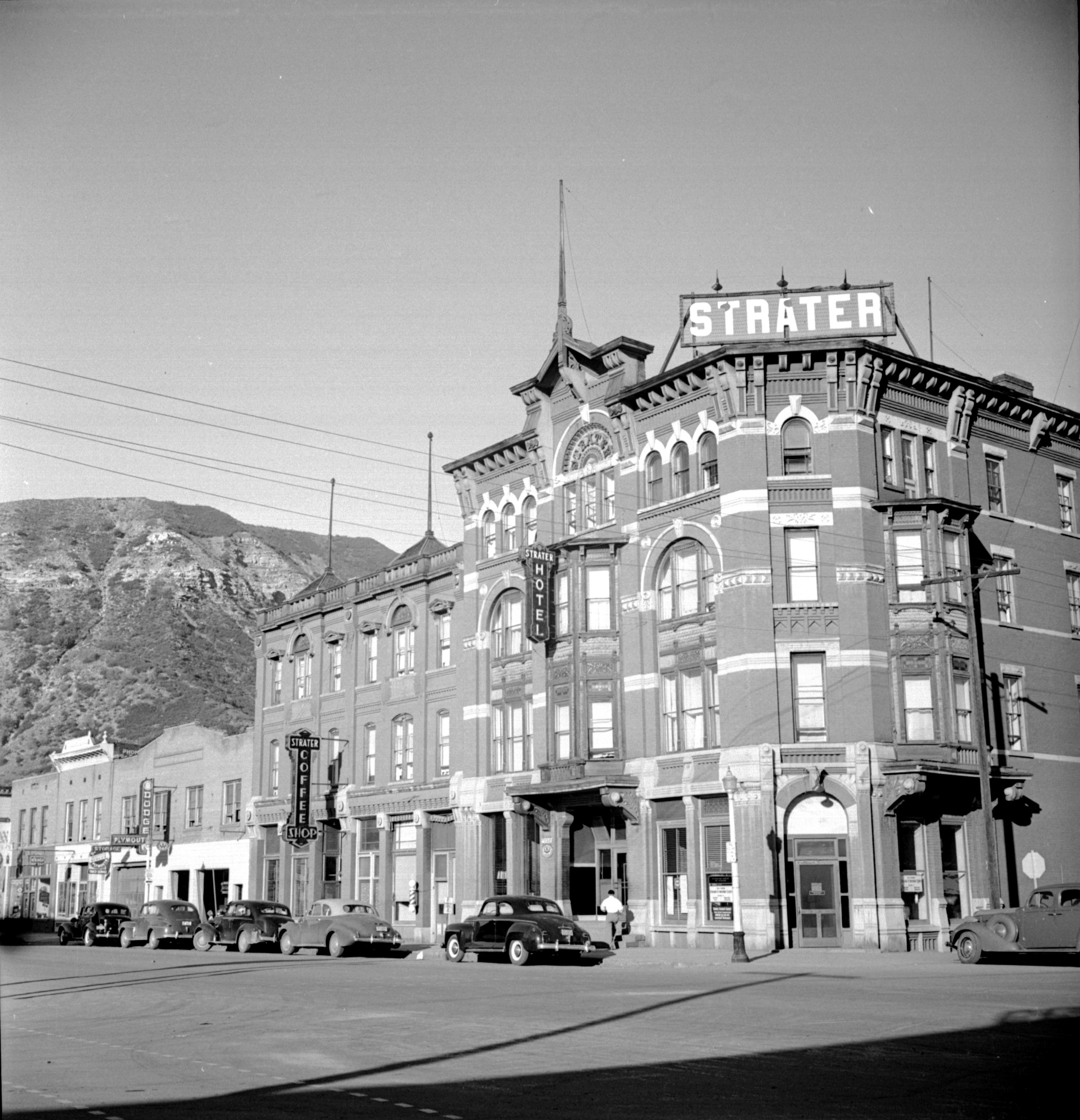 "Photo of a 4-story brick hotel building. The building in a dark brick with white detail. Many arched windows and an arched front door way on the corner decorate the building. A large sign on the roof above the front door says ""STRATER"" in large white block letters. Illuminated signs saying ""Strater Hotel"" and :Strater Coffee Shop"" hang from the side of the buildings. Cars are parked along the street in front of the building and someone is walking along the sidewalk."