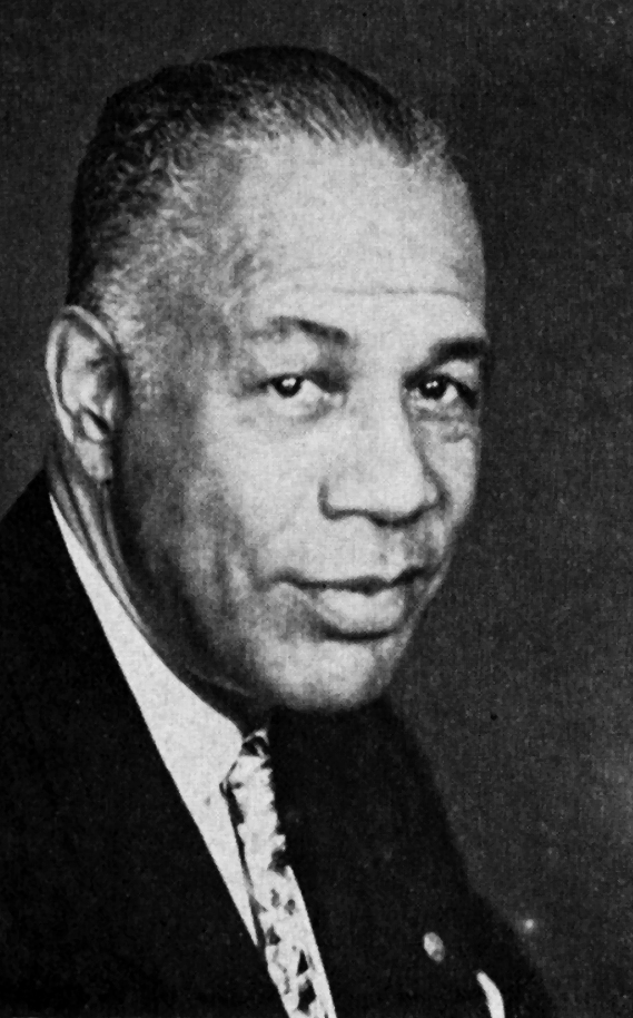 Photo taken in 1956, of an older African American man. This is a black and white close up portrait. He is dressed in a dark suit, white dress shirt, and patterned necktie. He has short hair that is combed back smoothly. He is looking at the camera and smiling.