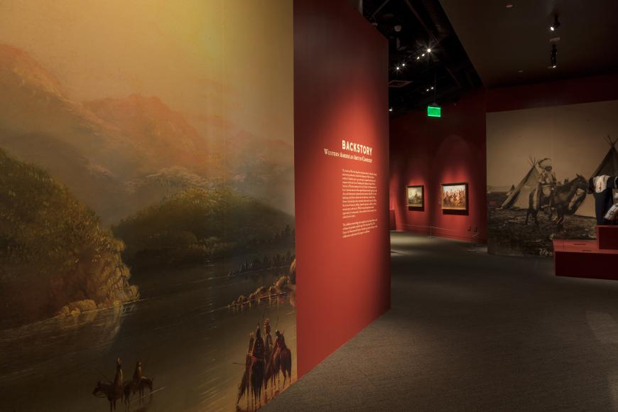 Inside Backstory exhibit, art hanging on red walls.