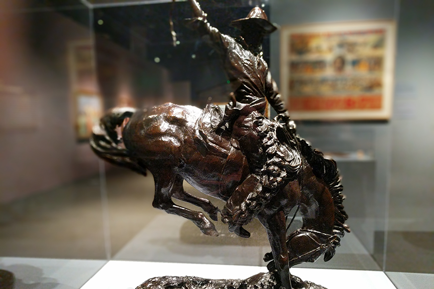 A bucking horse sculpture in a display case.