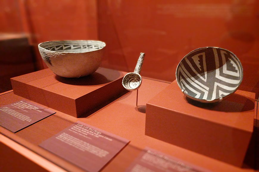 2 bowls and a ladle in a display case