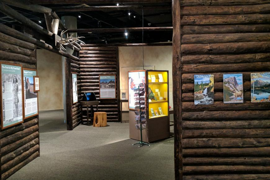 Side image of RMNP showing display cases and log cabin walls.