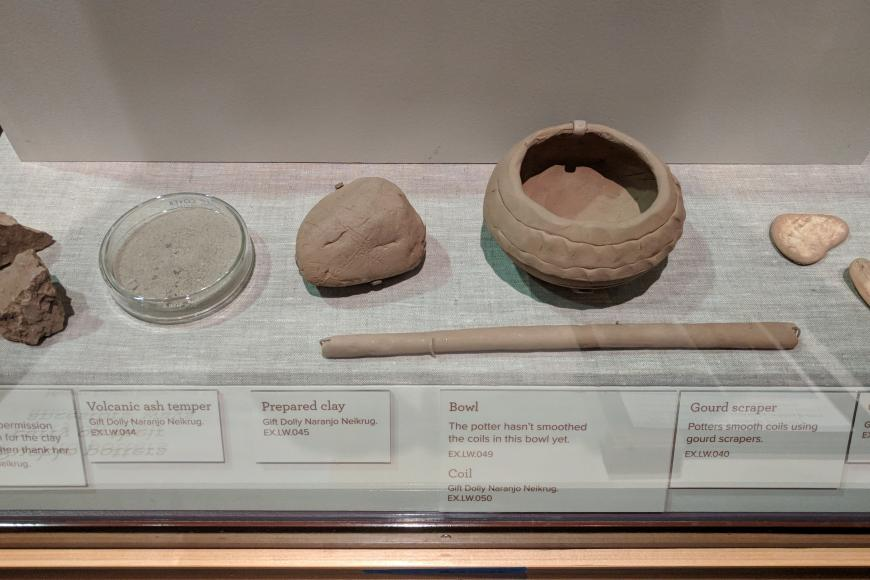 Display case showing the process of making clay for pottery.