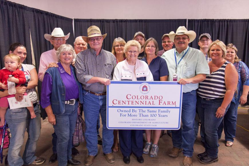 Allmer Farm & Ranch family with their Centennial Farm sign.