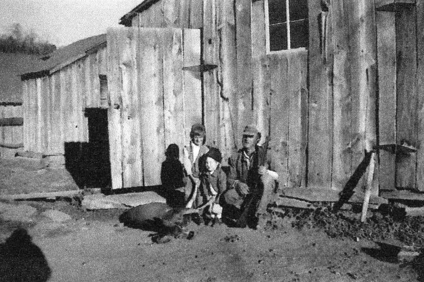 Clarence Everett and his two daughters outside the south barn with a deer carcass.