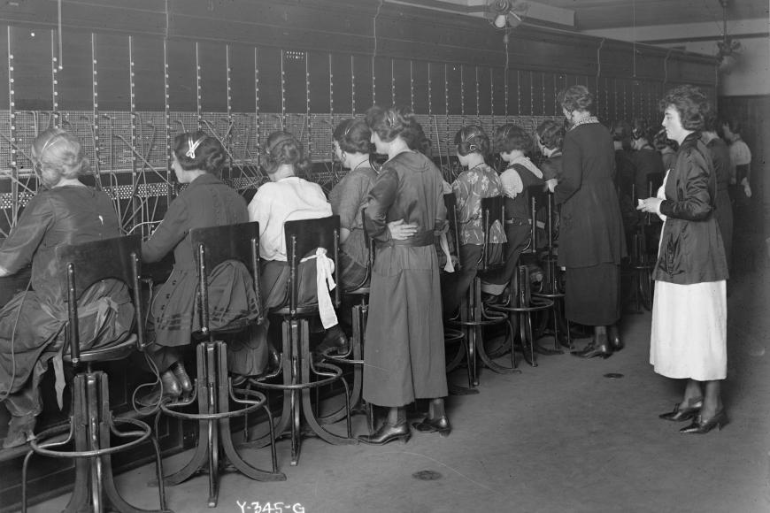 Teachers stand behind a group of students working at a switchboard