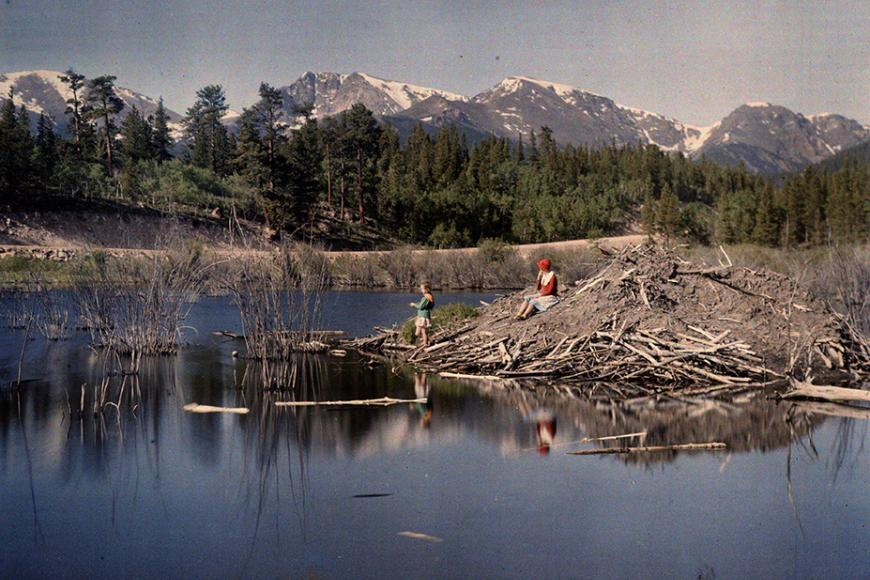 Autochrome image of Helen and Barbara Clatworthy sitting on a hill of dirt and debris in the middle of a lake, with the Rockies in the background.