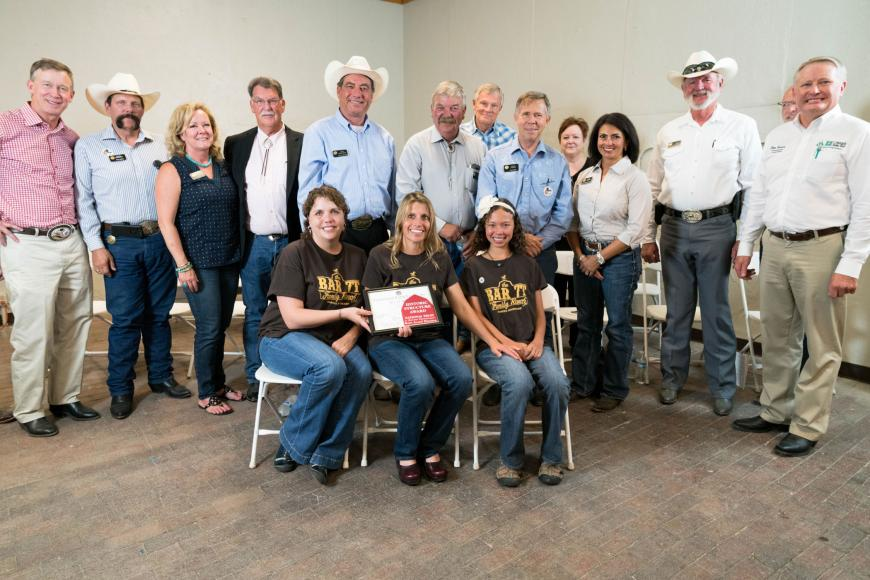 Bar 7T Ranch family (seated) with their certificate.
