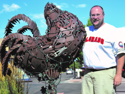 Photo of author Derek R. Everett, standing next to a sculpture of Mike the Headless Chicken, located in the town of Fruita, Colorado. The sculpture is made of reclaimed metal objects, such as a horseshoe, an axe, bolts, etcetera. It is a sunny day, with blue skies overhead, and the author is smiling, wearing a white Colorado baseball jersey with red lettering, and khaki pants.