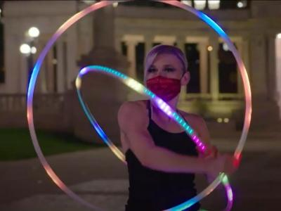 Photo of a woman in the middle of a hula hoop performance. She is using two hoops of different sizes, which are illuminated by multicolored LED lights. She is wearing a black sleeveless leotard and she is wearing a mask as a coronavirus precaution.