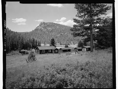 Photo of the McGraw Ranch buildings. In a clearing adjacent to large pine trees, sit three guest cabins and the laundry building, all of one-story log cabin design.