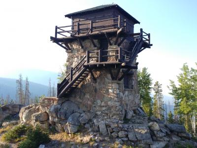 Photo of the stone and wood structure that is the Shadow Mountain Fire Lookout tower. It is a tall structure, square in shape, with a wooden deck and room that sits atop a stone base.
