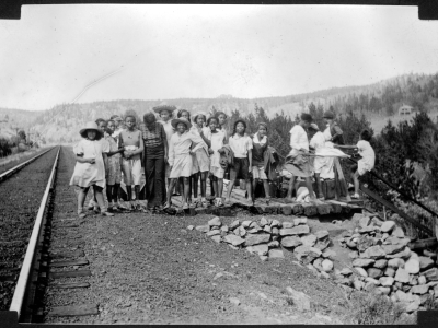 A group of African American teenage campers and their counselors from Camp Nizhoni pose by Denver & Rio Grande Western Railroad tracks and a railway stop near the entrance to Lincoln Hills (Gilpin County), Colorado. They wear dresses, blouses, shorts, and wide-brimmed hats; some hold jackets and coats. Shows luggage on a wooden platform.