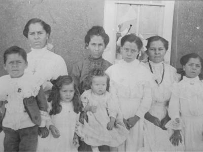 An historic photo of two women sitting amongst one boy and five girls, all ranging in ages from about one year old to teens.