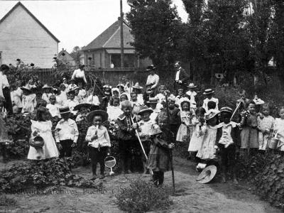 Kindergarten students at Bessemer School working in their school garden, 1902. Adults behind the class include teachers Miss Carrie Carlile, Miss Mary Williamson, and another unknown woman, most likely another teacher and Superintendent J. F. Keating.