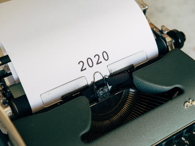 "Photo of an old Olympic typewriter, with a piece of white typing paper in it, which simply says ""2020"" in large black numerals."