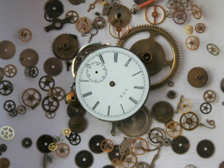 Photo of a white clock face with thin black roman numerals. The clock is in pieces, and all of the small cogs that make the clock function are scattered around in the area around the clock face.  The hands on the clock face are missing.