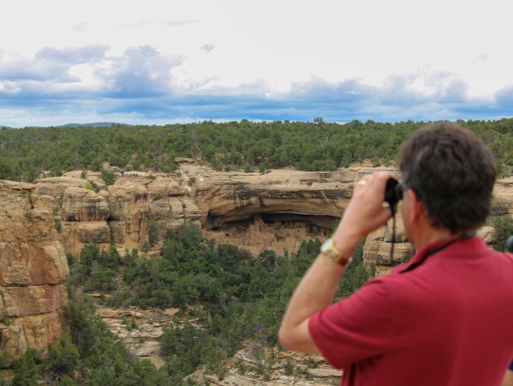A man looks at ruins with binoculars at Mesa Verde National Park