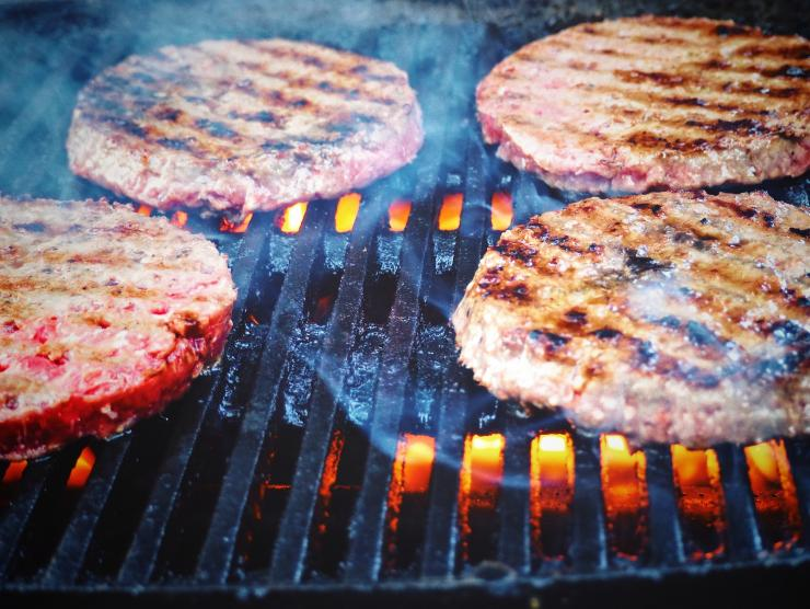 "Photo closeup of four beef hamburgers cooking on a grill.  The first side of the burgers has been cooked, because the tops of each burger patty have ""grill marks"" lining them. The orange grill flames are visible beneath the black cast iron grates of the grill and a few wisps of smoke are rising from the cooking surface."