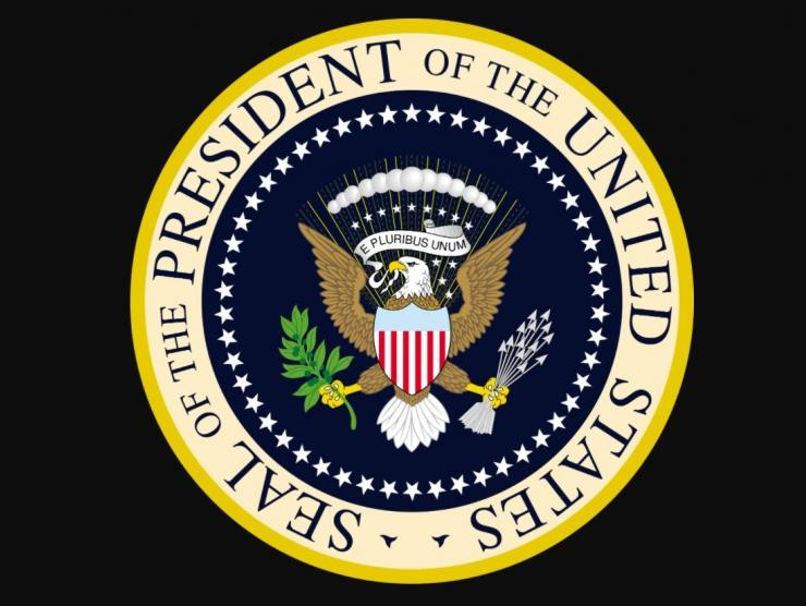 "Image of the seal of the President of the United States, as stated in a gold circle around the perimeter of a navy-colored circle depicting an eagle with a banner saying ""E Pluribus Unum"" in its mouth. Above its head & banner are 9 white stars & 13 white spheres. The eagle has a shield in front of its chest: it's blue at the top, red & white stripes on the bottom portion. The eagle holds an olive branch in its right talon, a bunch of arrows in its left talon. The navy color is encircled with white stars."