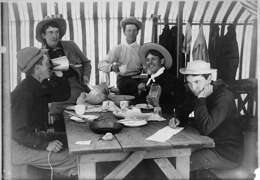 Five men in hats sit at a table having breakfast.