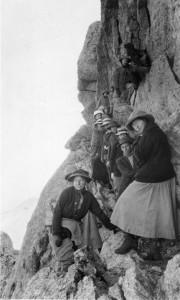 A group of men and woman pose beside a steep cliff near the summit of Longs Peak.