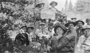 A group of men and women pose in the Clear Creek Basin region. Most of them are sitting on the ground, but two women stand in the back with a club sign.
