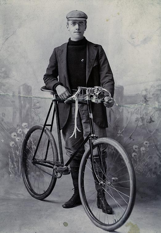 A studio portrait of Fred Payne Clatworthy with a bicycle