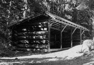 A black and white photo of the stable  with large log walls on the side and sloping overhang before a row of pine trees with snow on the ground before the stables.