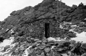 A black and white photo of the shack with tower next to it, and rocky peak in the background, in the foreground there is snow lain about sporadically.