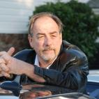 Photo of author  and local music historian, G. Brown. He is standing and leaning his elbows on the roof of a black car, and there is a white and stone building with green shrubs in the background.. He is wearing a black leather jacket, has a receding hairline of brown hair, and a brown and silver colored goatee and moustache.  He is looking off into the distance.