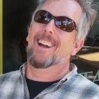 Photo of author Phil Carson. He is wearing a blue and gray plaid button-down collar shirt over a black crew neck t-shirt.  He has light brown-to-gray colored hair and a beard and mustache of the same.  He is pictured here on a bright day, wearing sunglasses and seems to be laughing.