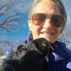 Photo of Cindy Nasky, with a dog. She looks to be hugging the dog, while the dog is looking off to its right and Cindy is looking at the camera. She is wearing a lightweight blue Patagonia jacket and aviator-style sunglasses Her hair is pulled back away from her face, and she is smiling. It is a sunny day, and the blue sky and treetops are visible behind her.