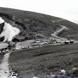 A black and white photo of the road with a parking lot in the center of the picture next to a structure and on the other end rolling into the hills in the distance.