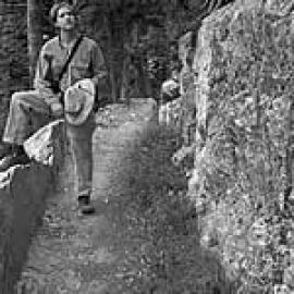 A black and white photo of part of the trail with rock on the right and a person holding a hat and propping their foot on the ledge on the left.