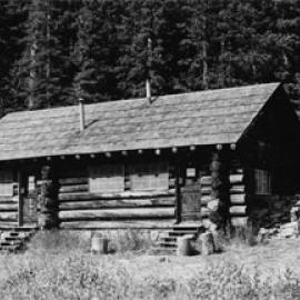 A black and white photo of the cabin with two doors and stairs leading up to them beneath overhanging roof. In the background are a wall of evergreen trees.