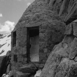 A black and white photo of the shelter with narrow entrance and stones leading up to it on the side of a mountain.