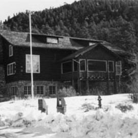 A photo of the lodge in black and white with snow in the foreground and forested mountains in the back.