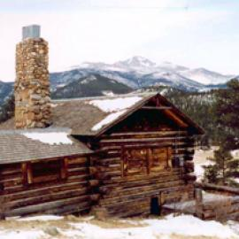 A view of the cabin with log walls and gabled roof and large stone chimney on the side in front of mountains in the distance.