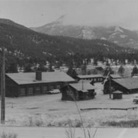 A black and white photo of some buildings in the district with snow lain in the foreground and rolling mountains in the background covered by trees.