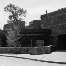 A black and white photo of the building with covered path and trees sticking up sporadically on the left side.